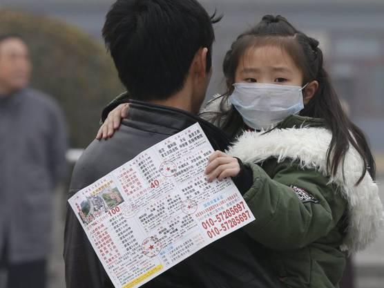 Mädchen in Peking mit Mundschutz