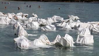 Mit weissen Tüchern im Meer wird den Verstorbenen gedacht