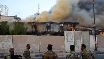 Über zahlreichen Regierungsgebäuden in Basra im Irak gibt es am Donnerstag dicke Rauchschwaden.