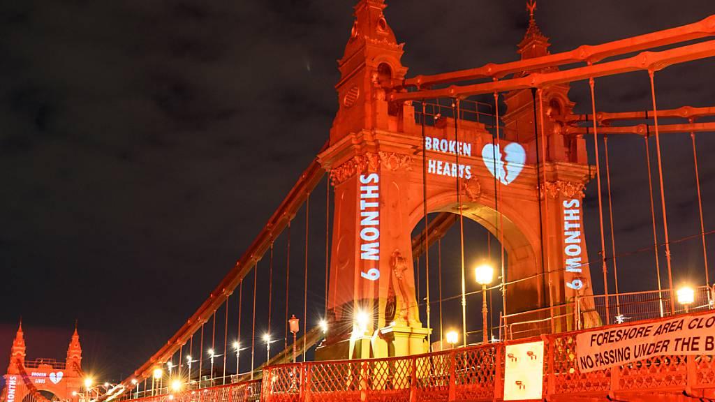 HANDOUT - Die Hammersmith-Brücke zeigt, die für den Valentinstags hellrot beleuchtet wurde, um auf die anhaltenden Verzögerungen bei der Reparatur hinzuweisen. Foto: Nigel Edwards/Hammersmith Bridge SOS/PA Media/dpa - ACHTUNG: Nur zur redaktionellen Verwendung im Zusammenhang mit der aktuellen Berichterstattung und nur mit vollständiger Nennung des vorstehenden Credits