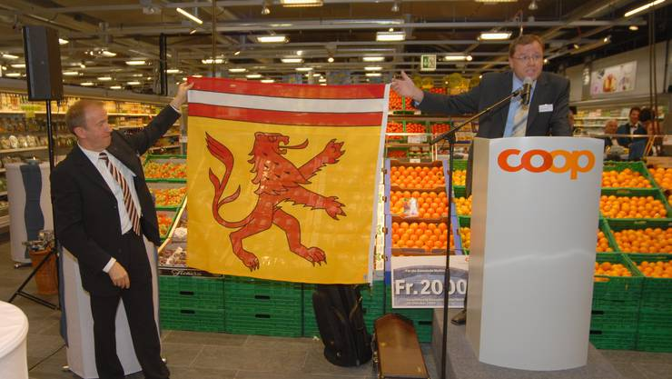 Geschenk: Gemeindeammann Bruno Gretener überreichte dem Leiter der Coop-Verkaufsregion Nordwestschweiz, André Mislin (links), eine Fahne von Mellingen. (Bild:: Walter Schwager)