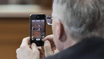 Ständerat Thomas Minder spielt mit seinem Handy.