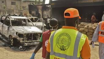 Helfer vor einem nach einem Anschlag ausgebrannten Auto in Kano (Archiv)