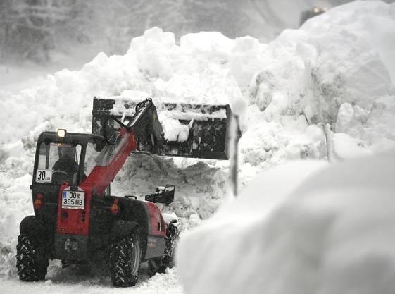 Ein Bagger befreit eine Strasse in Salzburg von den Schneemassen