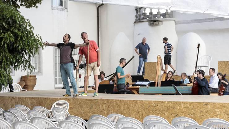 Die Sänger Michael Feyfar und Hans-Jörg Mammel beim Proben (v.l.) auf der Bühne vor Schloss Waldegg; im Hintergrund beobachtet Regisseur Georg Rootering (2.v.r.); im Orchestergraben dirigiert Andreas Reize.