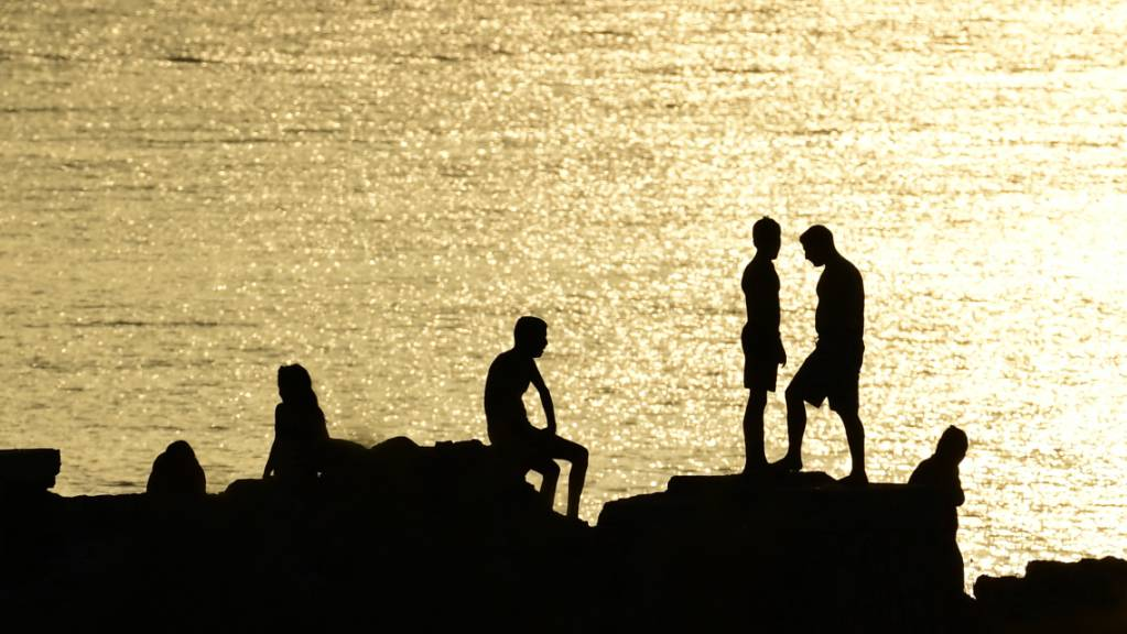 Menschen stehen auf Felsen in der Nähe eines Strandes im Vorort Kavouri. Die extreme Hitzewelle in Griechenland lässt nicht locker. Seit über einer Woche klettern die Temperaturen für mehrere Stunden täglich auf über 40 Grad. Foto: Michael Varaklas/AP/dpa