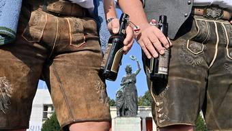 dpatopbilder - Zwei Männer in Tracht stehen mit Bierflaschen auf dem Wiesn-Gelände in München. Foto: Peter Kneffel/dpa
