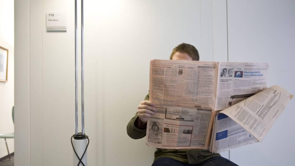Ein Arbeitsloser blättert in einem Stellenanzeiger (Symbolbild).