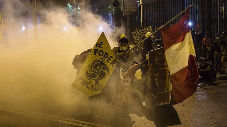 Demonstranten flüchten vor Tränengas, das von der Polizei eingesetzt wurde, um Demonstranten zu zerstreuen, die sich auf der Plaza San Martin versammelten, um gegen die Amtsenthebung des Ex-Präsidenten Vizcarra zu demonstrieren. Zum sechsten Tag in Folge hat es in Peru Demonstrationen gegen die Amtsenthebung des Ex-Präsidenten Vizcarra gegeben. Foto: Rodrigo Abd/AP/dpa