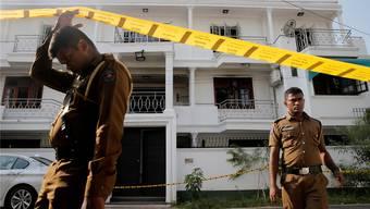 Polizisten vor dem Haus, in dem einer der Tatverdächtigen gewohnt hat.