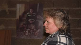 Susanne Blum vor dem Bild ihres verstorbenen Mannes, das – wie durch ein Wunder – unversehrt aus den Brandtrümmern geborgen werden konnte.