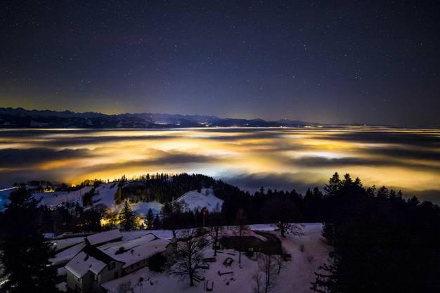 Nächtlicher Blick vom Bachtel auf das Zürcher Oberland, das unter dem Hochnebel liegt.