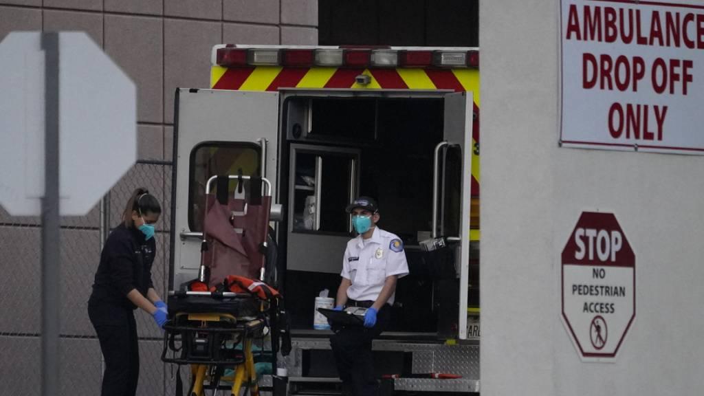 Rettungssanitäter desinfizieren einen Krankentrage nach dem Transport eines Corona-Patienten in Los Angeles. Foto: Damian Dovarganes/AP/dpa