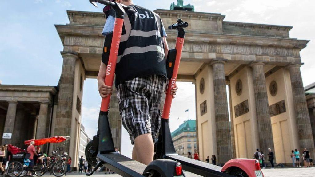 Ein Mitarbeiter einer E-Scooter-Verleihfirma schleppt vor dem Brandenburger Tor parkierte Trottis ab. (Archivbild)