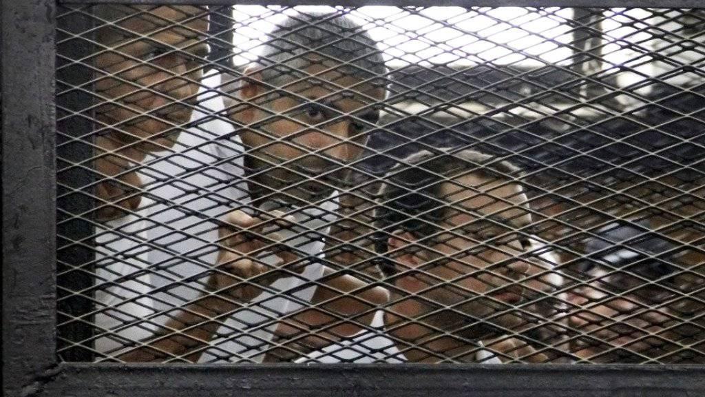Der Australier Peter Greste und der Kanadier Mohammed Famy bei ihrem ersten Prozess in einem Angeklagten-Käfig vor Gericht in Kairo. (Archiv)