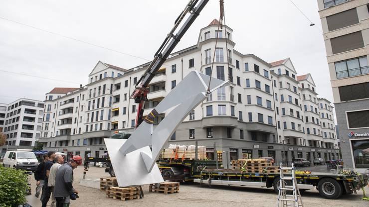 Das 3,7 Tonnen schwere Kunstwerk aus Chromstahl, die auf dem Lastwagen lag, wird langsam aufgestellt und auf Holzpaletten abgestellt.