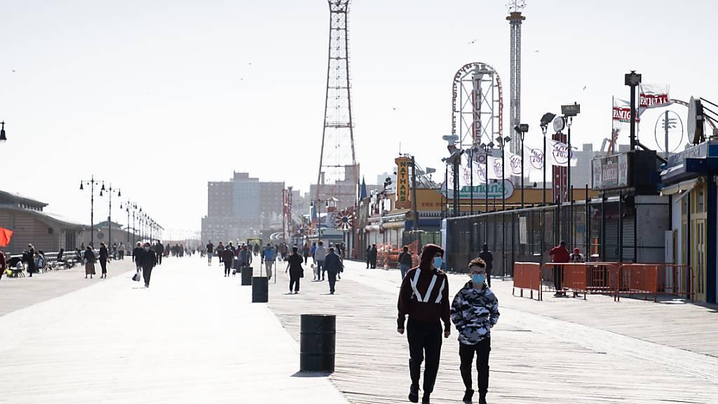 ARCHIV - Passanten mit Mundschutzen spazieren die Strandpromenade von Coney Island in New York entlang. Foto: Braulio Jatar/SOPA Images via ZUMA Wire/dpa