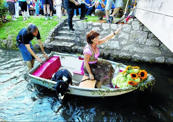 Moderatorin Monika Fasnacht fuhr samt Hund Simba mit dem Boot auf dem Dorfbach vor (Bild: ae)