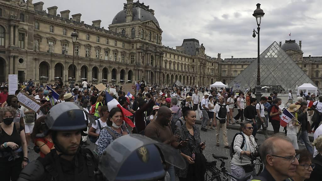 Demonstranten und Demonstrantinnen nehmen vor dem Louvre-Museum in Paris an einem Protest gegen den Gesundheitspass teil. Foto: Adrienne Surprenant/AP/dpa
