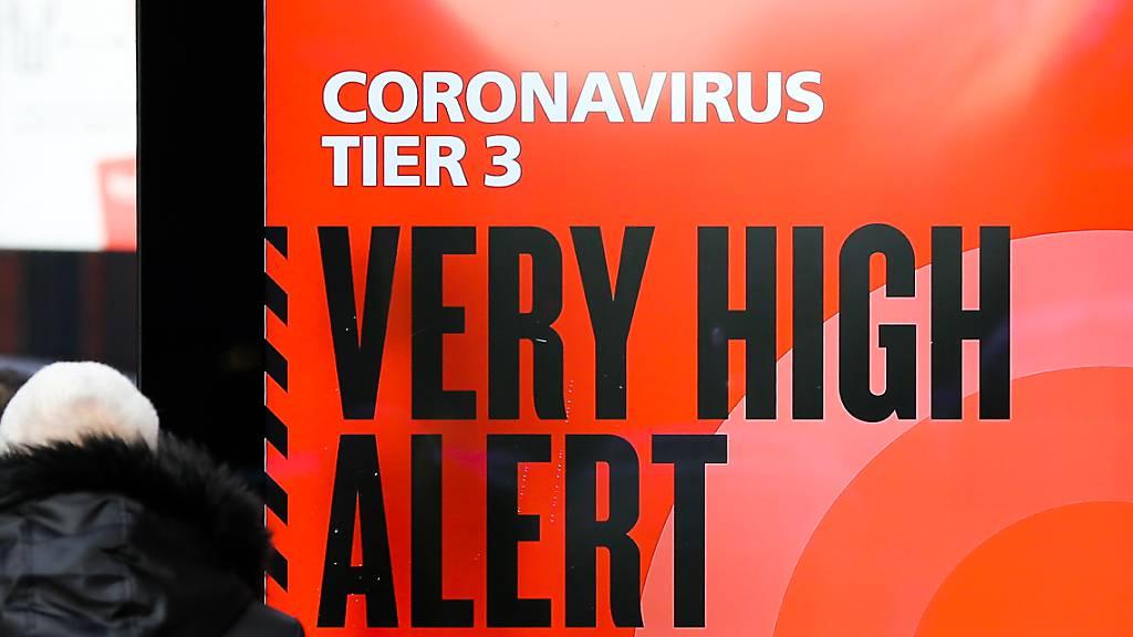 Ein Plakat des britischen Gesundheitsdienstes NHS mit der Aufschrift «Coronavirus Tier 3. Very high alert» (Coronavirus Stufe 3. Sehr hohe Alarmstufe) steht in der Londoner Innenstadt.