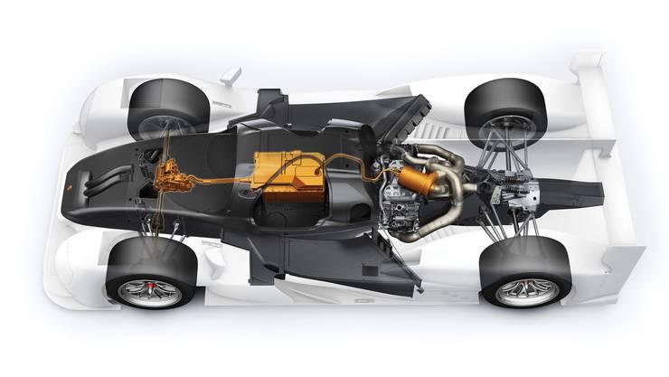 Der Verbrennungsmotor sitzt direkt hinter dem Fahrer und treibt die Hinterräder an. Eine Turbine generiert aus dem Abgasstrom zudem elektrische Energie, die in der Batterie gespeichert wird. Diese liegt direkt neben dem Fahrer. Der E-Motor liegt vorne und triebt die Vorderachse an. Beim Bremsen kann er Energie zurückgewinnen.
