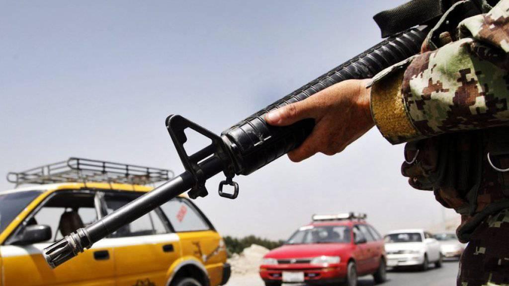 Ein Mitglied der afghanischen Sicherheitskräfte kontrolliert eine Strasse in Kabul. Die Sicherheitsvorkehrungen waren nach der Bekanntgabe des Todes von Mullah Omar verstärkt worden