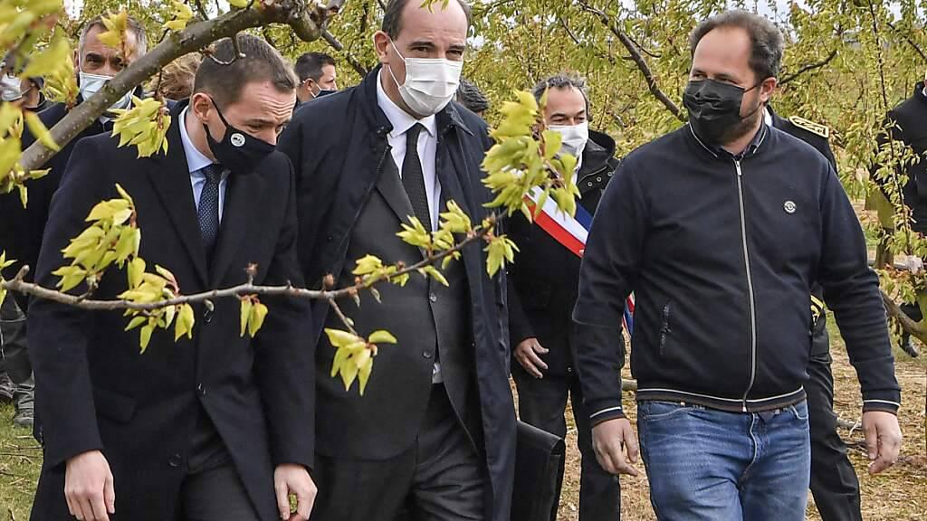 Jean Castex (M), französischer Premierminister, wird vom Landwirtschaftsminister Julien Denormandie (l) und dem Landwirt Gilbert Pasquio (r) begleitet, als er eine Aprikosenplantage besucht, deren Bäume durch die jüngsten Nachtfröste beschädigt wurden. Nach frostigen Nächten fürchten Frankreichs Winzer und Obstbauern um ihre Ernte. Foto: Philippe Desmazes/AFP/dpa