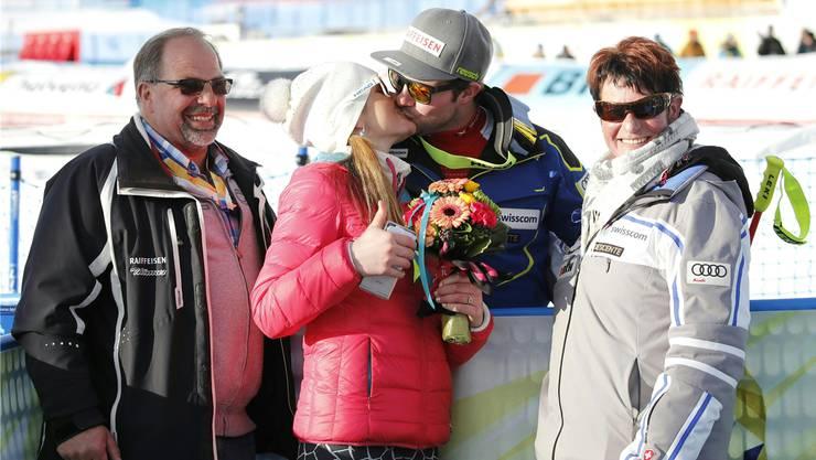 Der Siegeskuss: Katrin Triendl und Weltmeister Beat Feuz. Daneben strahlen Vater Hans und Mutter Hedi vor Glück.