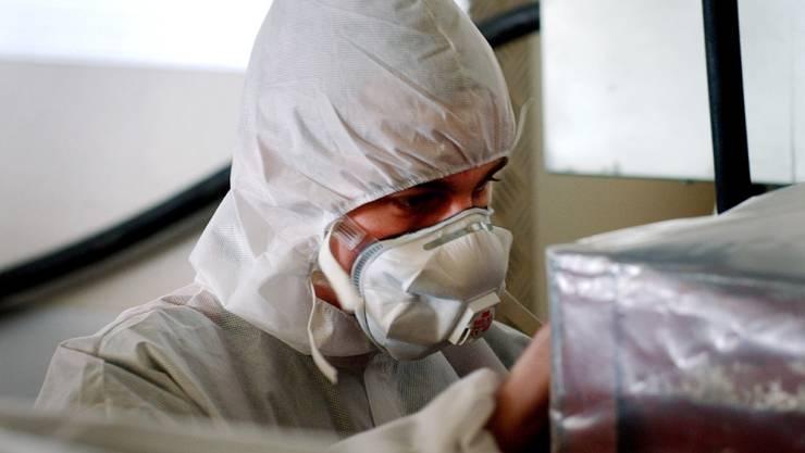 Ein Arbeiter mit Mundschutz und Schutzkleidung bereitet eine Abfallkiste voll asbestverseuchtem Material auf ihren Abtransport vor. (Archivbild)