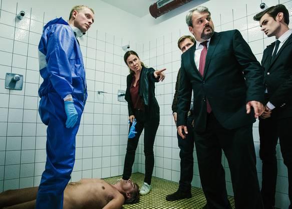 In einer Dusche im Brügglifeld liegt ein toter Schiedsrichter. Um ihn herum stehen Gerichtsmediziner Dr. Alois Semmelweis, Kommissarin Anna-Maria Giovanoli, Kommissar Reto Doerig, sowie die Bestatter Luc Conrad und Fabio Testi.