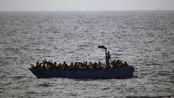 Flüchtlinge in einem Holzboot vor der libyschen Küste. Von Libyen aus wagen die meisten Flüchtlinge die Fahrt über das Mittelmeer nach Europa. (Archiv)