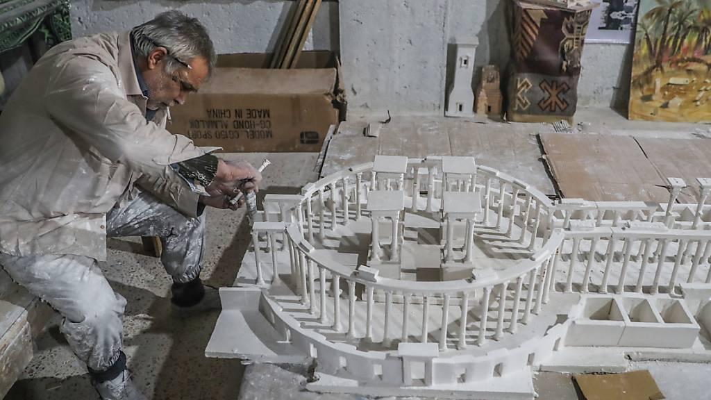 Ali Alsaleh in seiner Werkstatt bei der Arbeit an seinem Modell der antiken Oasenstadt Palmyra. Foto: Anas Alkharboutli/dpa
