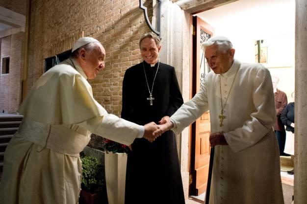 Papst Franziskus und sein Vorgänger Benedikt XVI. reichen sich zur Begrüssung die Hand.