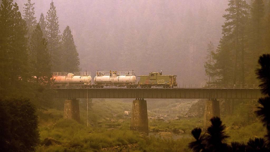 Ein Löschzug versprüht in Plumas County Löschmittel auf Gleise und umliegendes Land. Foto: Noah Berger/AP/dpa
