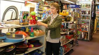 Brigitte Carlyle ordnet die neuen Spielwaren auf den Gestellen – früher wurde dort Zubehör für Modelleisenbahnen präsentiert. Die Gleisanlage steht bereit zum Abtransport (hinten links). Dieter Minder