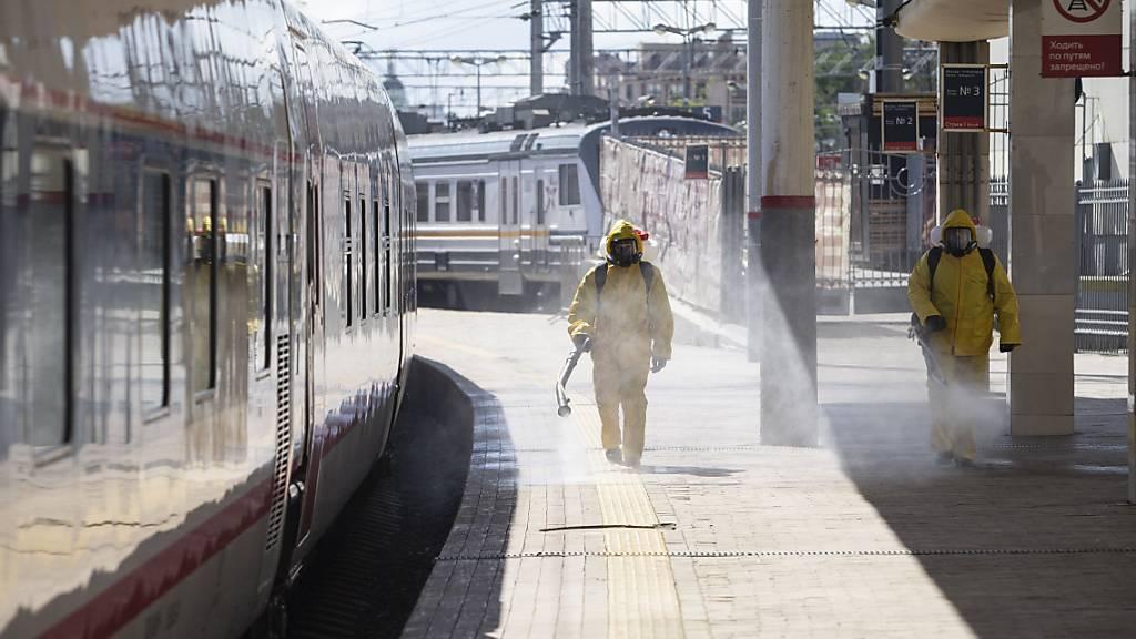 Staatliche Mitarbeiter in Schutzkleidung desinfizieren den Kiewer Bahnhof in Moskau. Foto: Alexander Zemlianichenko Jr/AP/dpa
