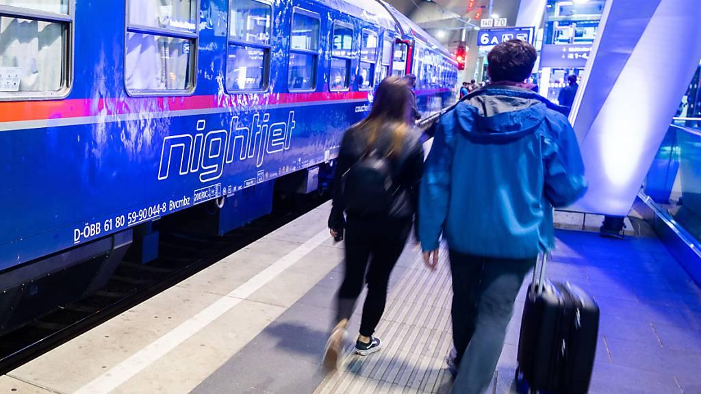 ARCHIV - Passagiere gehen neben einem Zug der ÖBB auf einem Gleis im Wiener Hauptbahnhof. Foto: Georg Hochmuth/APA/dpa