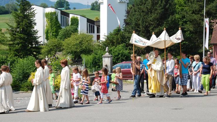 Ministrantinnen und Ministranten sowie Blumen streuende Kinder gehen in Aedermannsdorf dem Priester mit der Monstranz unter dem Baldachin voraus.