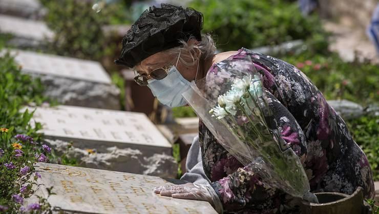 Eine Frau mit Schutzmaske und Handschuhen am Grab ihres Bruders: Israel gedenkt inmitten der Corona-Krise seiner getöteten Soldaten und Terroropfer.