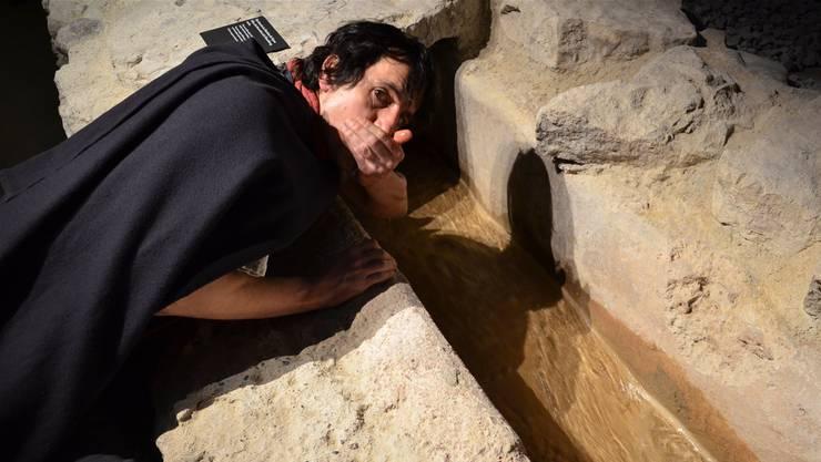 Nur ein Teilstück der römischen Wasserleitung liegt frei. Ein Legionär schöpft daraus Wasser und stillt seinen Durst.