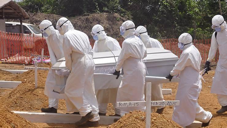 Sanitäter tragen den Sarg eines wegen Ebola gestorbenen Menschen über einen Friedhof in Liberia (Archiv)