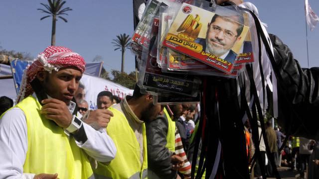 Ein Verkäufer bietet Plastikkarten mit dem Gesicht von Präsident Mursi feil vor der Universität in Kairo