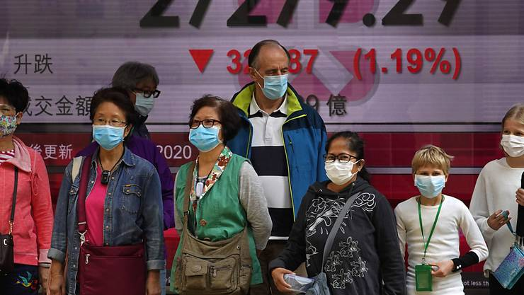 Die Furcht vor dem Coronavirus kommt nun immer stärker an den Börsen an - im Bild Passanten vor der Hong Kong Stock Exchange. (Archiv)