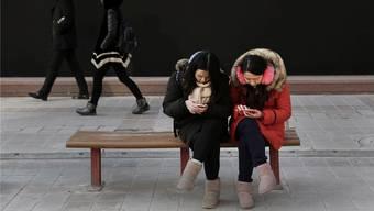 Orwellsche Dimension: Handynutzerinnen in Peking. K. Frayer/Getty