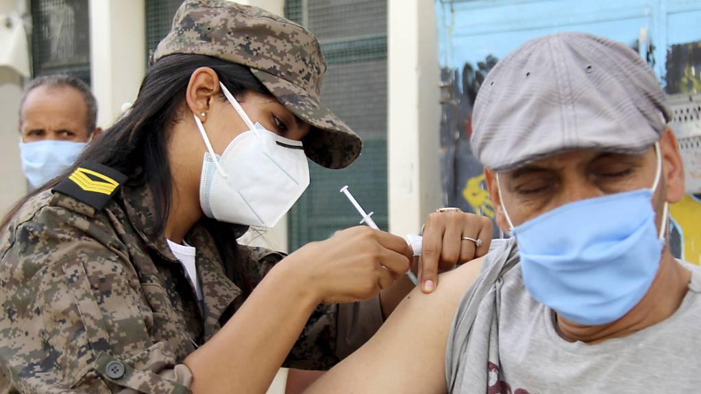 Eine Soldatin verabreicht einem Mann in der Assad-Iben-El-Fourat-Schule den Corona-Impfstoff Vaxzevria während einer Impfaktion. Um die katastrophale Corona-Lage in Tunesien in den Griff zu bekommen, hat eine Impfaktion für bis zu eine Million Bürger im Land begonnen. Foto: Hassene Dridi/AP/dpa