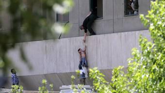 Menschen flüchten aus dem iranischen Parlament in Teheran.