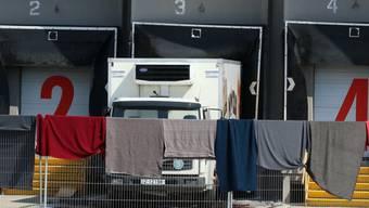 Tücher verdecken den Lkw, in welchem 71 tote Flüchtlinge entdeckt worden waren. Die österreichische Polizei hat unterdessen ein Ermittlungsteam nach Ungarn geschickt, von wo der Lastwagen losgefahren war