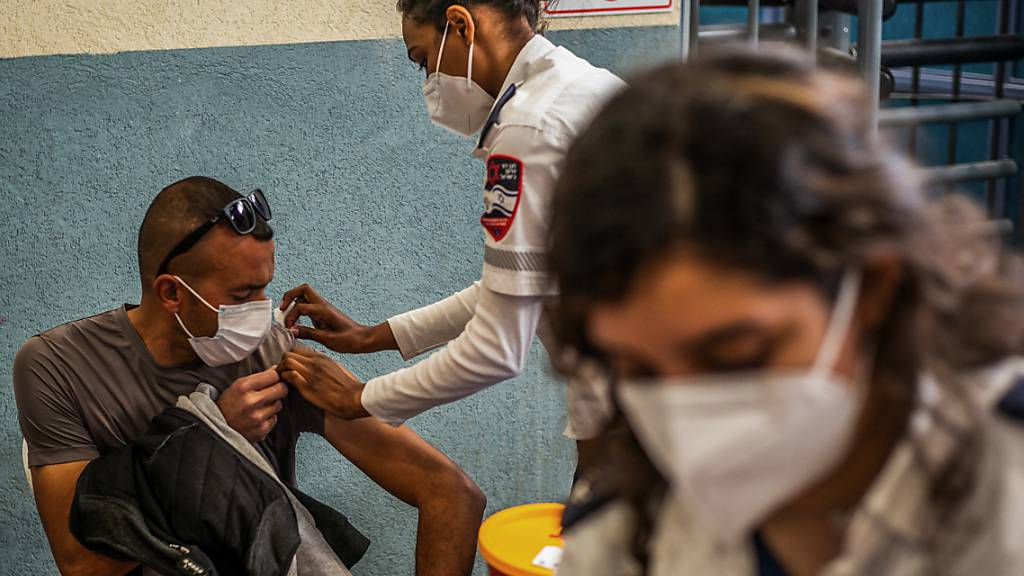 Eine medizinische Angestellte verabreicht einem palästinensischer Grenzgänger eine Corona-Schutzimpfung. Am Grenzübergang von Meitar wurde eine Impfzentrum errichtet. Foto: Ilia Yefimovich/dpa