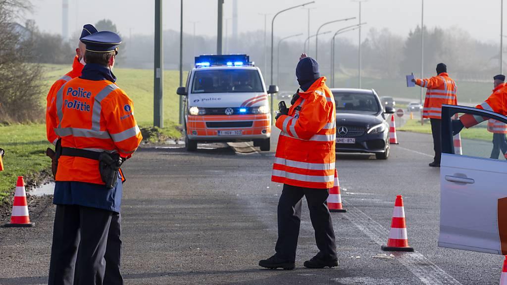 Polizisten halten während einer Kontrolle am Parkplatz Aire de Hondelange an der Autobahn E411 ein Fahrzeug an. Belgien kontrolliert seit dem 01.01. verstärkt Einreisende. Foto: Nicolas Maeterlinck/BELGA/dpa
