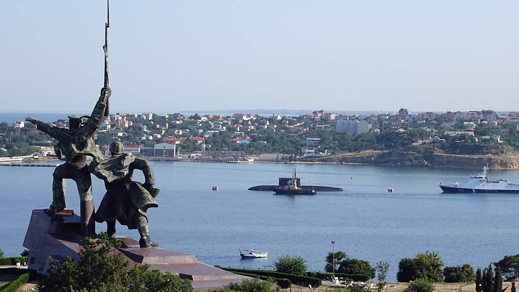 ARCHIV - Hinter einem sowjetischen Denkmal liegen ein U-Boot und Kriegsschiffe der russischen Schwarzmeerflotte vor Anker in der Hafenstadt Sewastopol. (Archivbild) Foto: Ulf Mauder/dpa